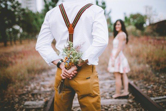 muž držící za zády kytici